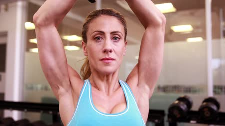 hatalom : Super fit woman lifting dumbbells at crossfit at the gym