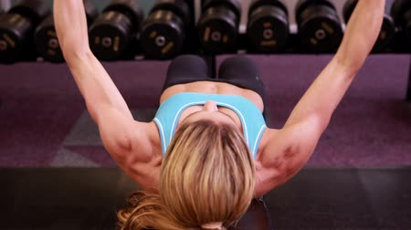 musculação : Super fit woman lying on bench lifting dumbbells at crossfit at the gym