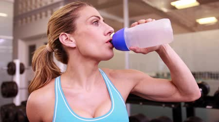 атлетика : Super fit woman drinking from water bottle and smiling at the gym Стоковые видеозаписи