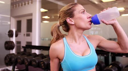 мышцы : Super fit woman drinking from water bottle at the gym