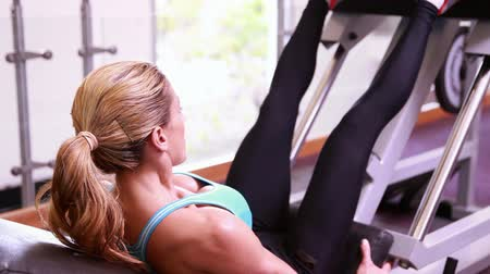 levantamento de pesos : Super fit woman using the leg weights machine at the gym