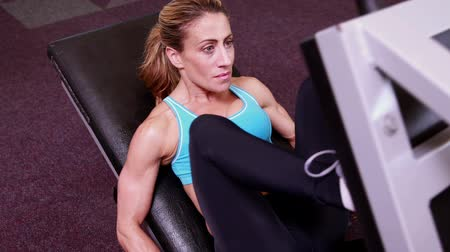 musculação : Super fit woman using the leg weights machine at the gym