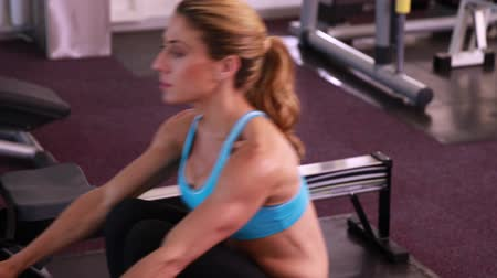 atletika : Fit woman using the rowing machine at the gym