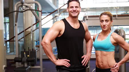 orta yetişkin kadın : Super fit friends smiling at the camea at the gym Stok Video