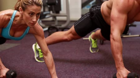 Two fit people lifting dumbbells in plank position at the gym