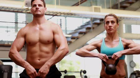 eğitici : Two fit people lifting kettle bells together at the gym