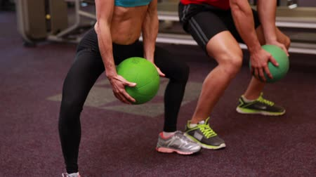 eğitici : Two fit people squatting with medicine balls at the gym Stok Video