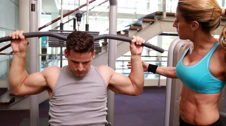 атлетика : Fit man using the weights machine for his arms while trainer supervises at the gym