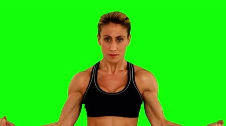 бицепс : Super fit woman flexing her arms on green screen background