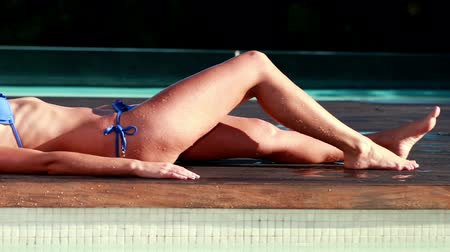 à beira da piscina : Sexy blonde in blue bikini relaxing lying poolside on a sunny day