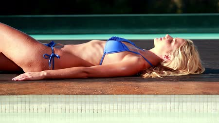 banhos de sol : Sexy blonde in blue bikini relaxing lying poolside on a sunny day