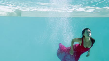 potápění : Brunette in evening gown diving into swimming pool on her holidays