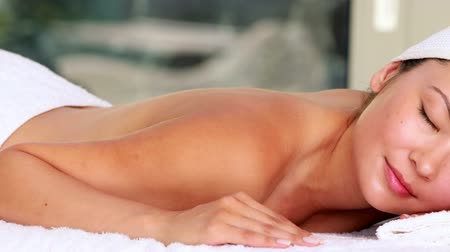 estância termal : Beautiful brunette lying on massage table smiling at camera in the health spa