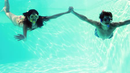 plunging : Happy couple jumping in swimming pool together wearing snorkels on their holidays Stock Footage