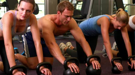 сильный : Kettlebell class getting into plank position at the gym