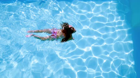 отель : Overhead of brunette swimming in pool on sunny day on her holidays