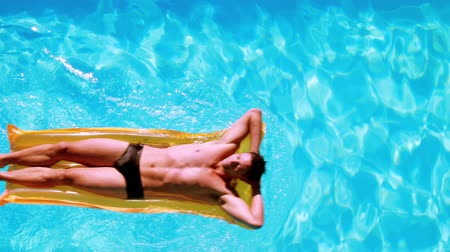 adam : Fit man relaxing on lilo in swimming pool on a sunny day Stok Video