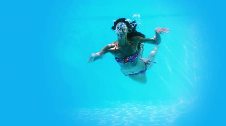 uszoda : Pretty brunette swimming underwater in pool on her holidays Stock mozgókép