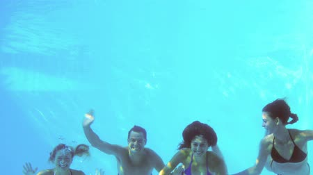 swimming underwater : Four friends jumping into swimming pool and waving on their holidays