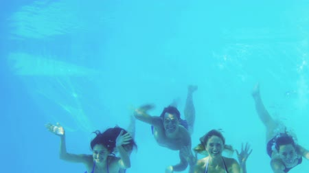 uszoda : Four friends jumping into swimming pool and waving on their holidays