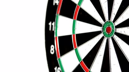 цель : Green dart missing the bullseye on white background in slow motion