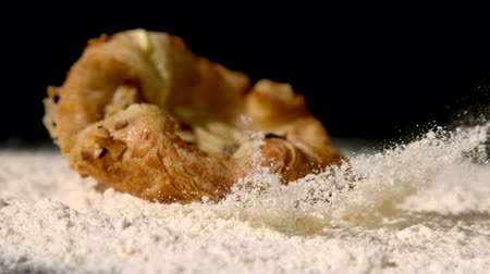 pastry : Pastry snack falling on flour on black background in slow motion