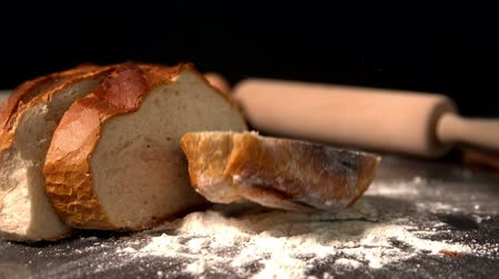 хлеб : Sliced loaf of bread falling on flour  in slow motion