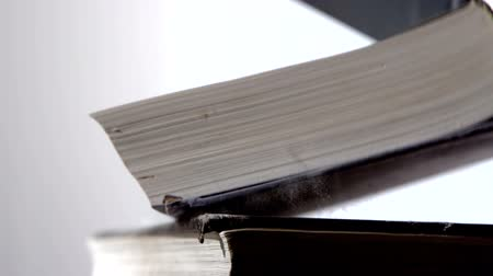 poros : Heavy black books falling on white surface in slow motion Stock mozgókép
