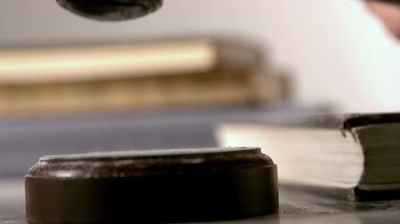 árverezői kalapács : Gavel falling on sounding block beside books in slow motion