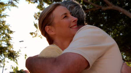 átölelő : Senior couple hugging on sunny day in slow motion
