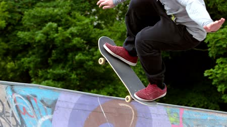 trik : Young skateboarder skating the outdoor skatepark in slow motion