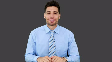 mluvení : Young businessman talking to camera on grey screen background
