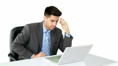 apprehensive : Young businessman working at his desk on white background