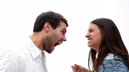 sinir : Angry young couple shouting at each other on white background Stok Video