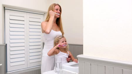 зубы : Cute little girl brushing her teeth with her mother at home in bathroom