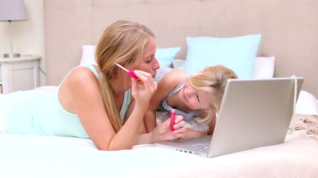 smích : Mother and daughter lying on bed using laptop at home in bedroom