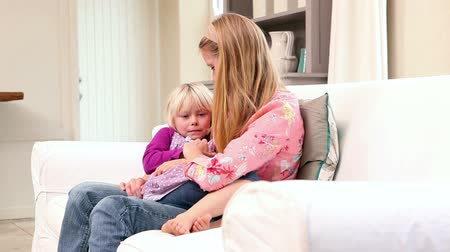 family life : Cute little girl sitting with mother on the couch at home in living room