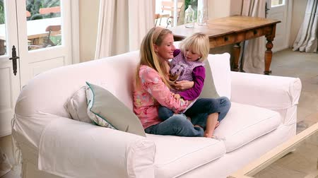 hozzábújva : Cute little girl hugging her mother on the couch at home in living room Stock mozgókép