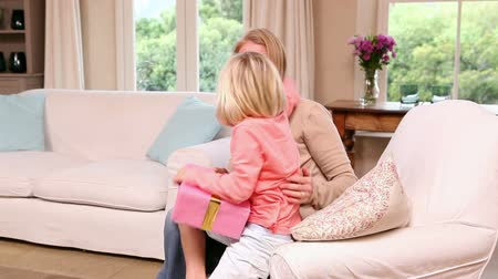 receber : Cute little girl getting a present from her mother at home in living room