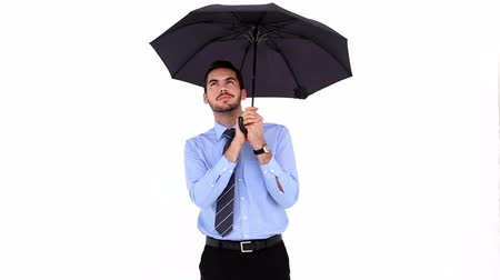 realizing : Young businessman sheltering with umbrella and putting it down on white background Stock Footage