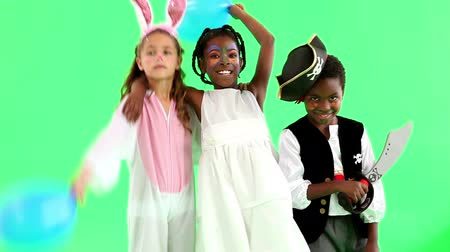 kostüm : Cute children dressed up in costumes on green background Stok Video