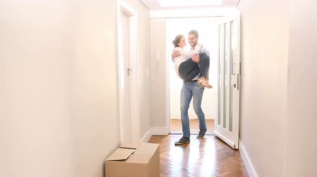 transportar : Man carrying his wife inside in their new home