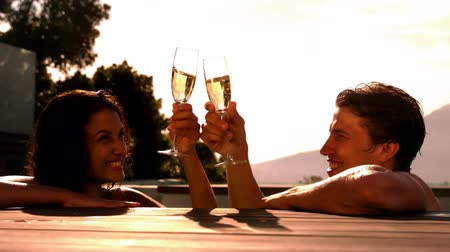 champagne pool : Happy couple drinking champagne together in the swimming pool in slow motion Stock Footage