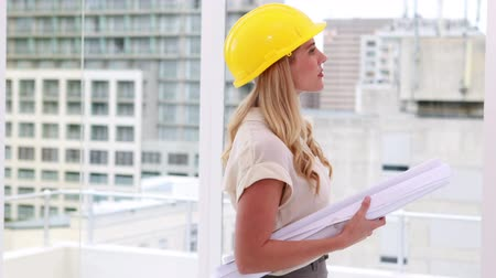 helmets : Pretty architect smiling to camera in the office Stock Footage