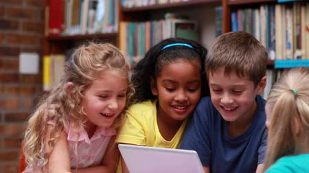 educar : Pupils using the tablet pc together in the library in elementary school
