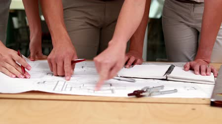 planos : Team of architects studying blueprints in the office Stock Footage