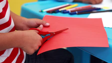 makas : Cute little boy cutting paper shapes classroom in playschool
