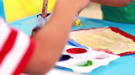 anaokulu : Cute little boys painting at table in classroom in playschool Stok Video