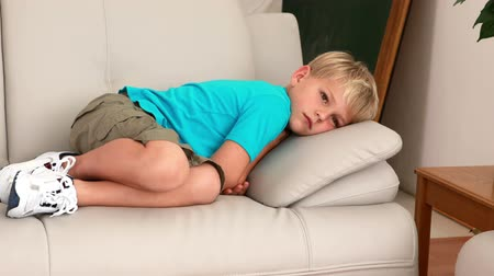lonely : Sad little boy lying on the couch at home in the living room Stock Footage