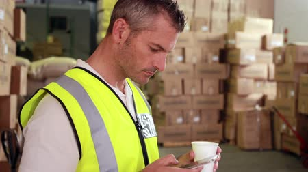 munkás : Warehouse worker sending a text on his break in a warehouse  Stock mozgókép